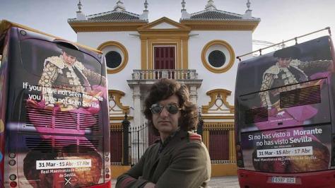 Morante de la Puebla posa en la Puerta del Príncipe de la Maestranza en medio de dos autobuses con la publicidad en inglés y en español, con una fotografía obra de nuestro compañero Ignacio Gil
