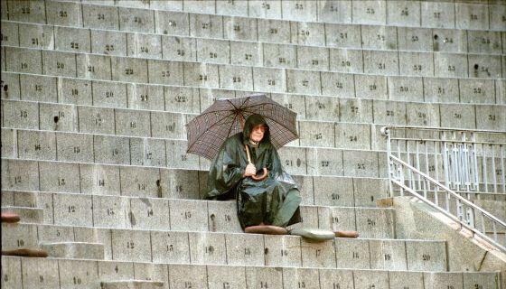 Joaquín Vidal, con capa y paraguas bajo la lluvia, en la plaza de toros de Las Ventas, en octubre de 1999. / CLAUDIO ÁLVAREZ